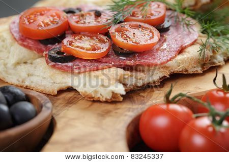 flat pita bread with salami and vegetables on wood table