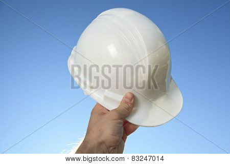 A hand holding a foreman helmet over the sky