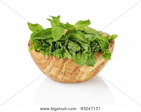 bunch of fresh spearmint in wood bowl isolated on white