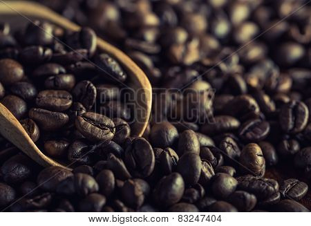 Coffee beans with a wooden ladle.