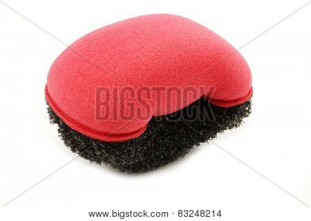 red plastic and foam abrasive pad on a white background