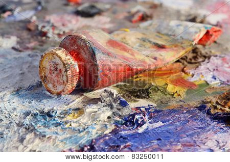 Closeup Of Old Oil Paint Tube With Red Colour Lying On Dirty Artistic Palette