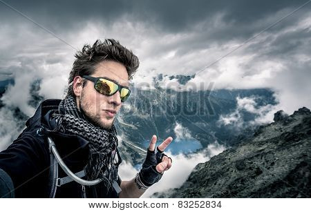 Disheveled man, with tousled hair on top of the mountain