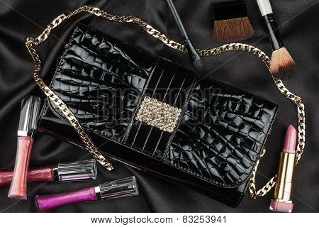 Beautiful Bag From Patent Leather And Cosmetics Lying On Black Satin