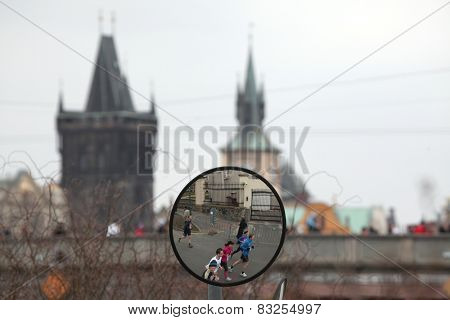 PRAGUE, CZECH REPUBLIC - APRIL 6, 2013: Convex mirror with the reflection of athletes running the Prague international marathon in Prague, Czech Republic. The Charles Bridge is seen in the background.