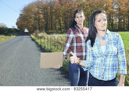 Two Womans asking for a hitch hicking on the road