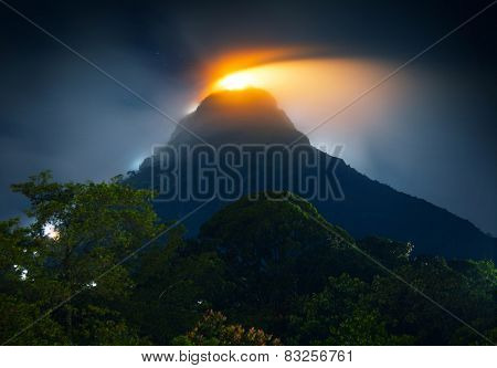 Mountain Adam's Peak (Sri Pada) covered by thick fog highlighted by illumination of the temple. Sri Lanka