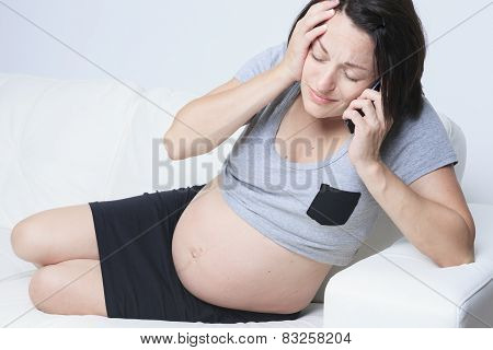 Pregnant woman sitting on the sofa with a telephone