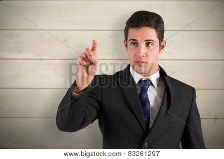 Businessman standing and pointing against bleached wooden planks background
