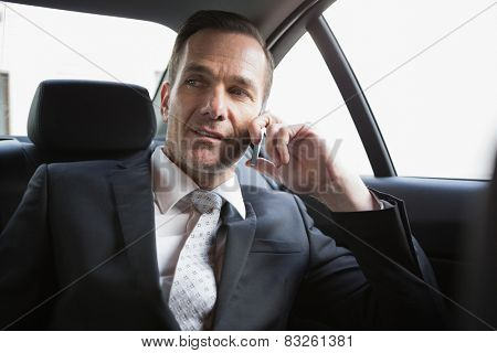 Handsome businessman making a phone call in his car