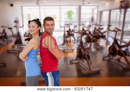 Fit man and woman smiling at camera together against large empty fitness studio with spin bikes