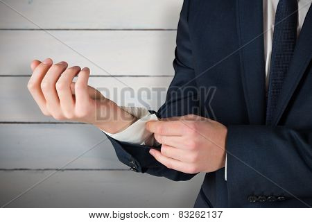 Businessman adjusting his cuffs on shirt against painted blue wooden planks