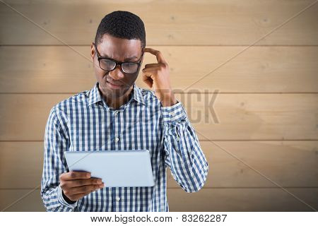Young businessman thinking and holding tablet against bleached wooden planks background