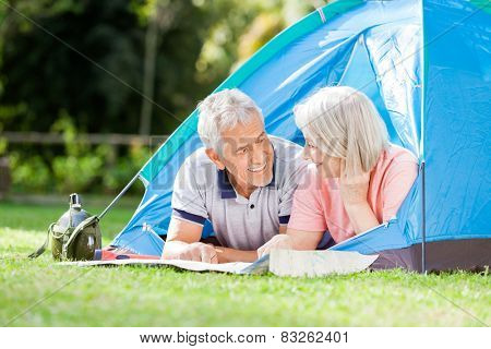 Senior couple looking at each other while studying map in tent at park