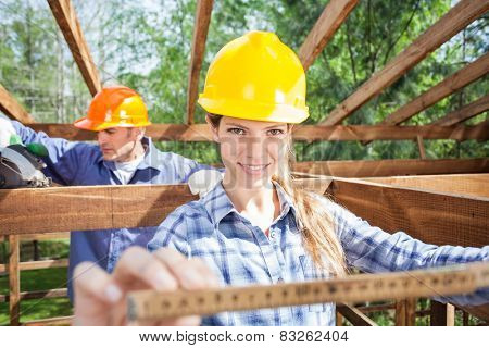 Portrait of smiling female architect holding measure tape while worker working in background at construction site