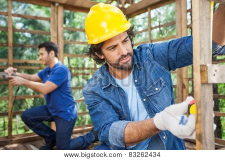 Male carpenter measuring wooden plank with tape while colleague working in background at construction site