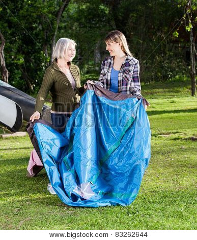 Happy mother and daughter making tent in park at campsite