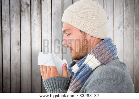 Handsome man in winter fashion blowing his nose against wooden planks