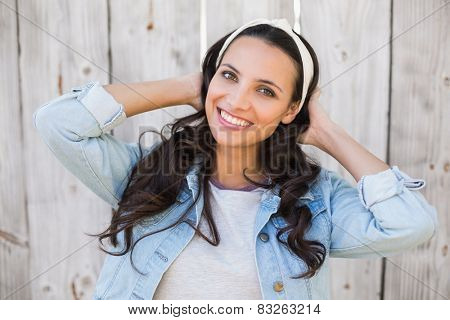 Pretty hipster smiling at camera against bleached wooden fence