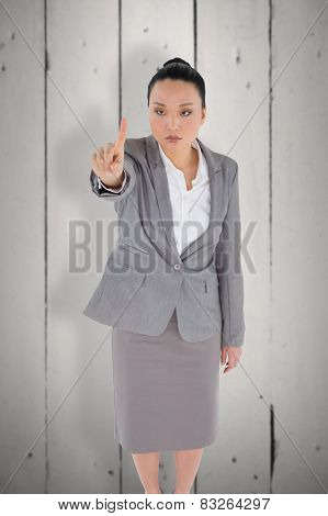 Unsmiling asian businesswoman pointing against white wood
