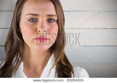 Serious young woman in white shirt against painted blue wooden planks