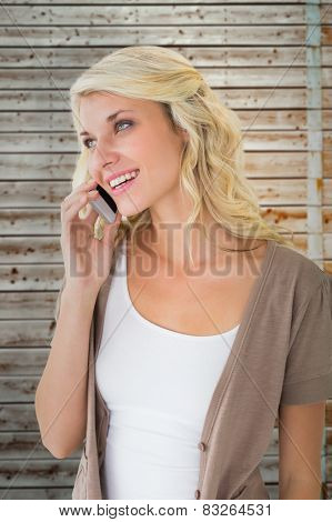 Attractive blonde talking on her smartphone against faded pine wooden planks