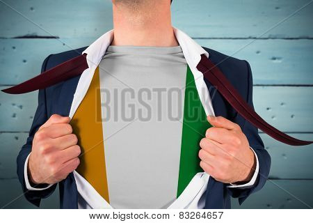 Businessman opening shirt to reveal ivory coast flag against painted blue wooden planks