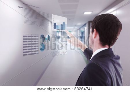 Focused businessman standing and pointing against college hallway
