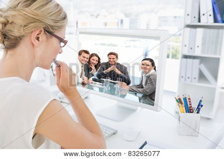 Portrait of a positive manager with his team against rear view of a female photo editor working on computer