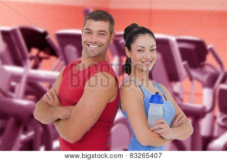 Fit man and woman smiling at camera together against close up of treadmills in a fitness centre