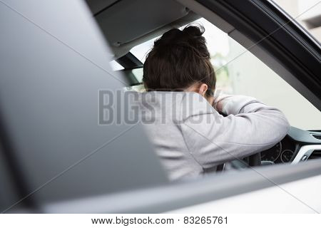 Woman sleeping on the wheel in her car