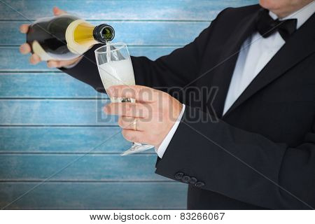 Man in suit pouring champagne against wooden planks