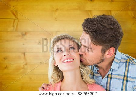 Handsome man kissing girlfriend on cheek against wooden planks background