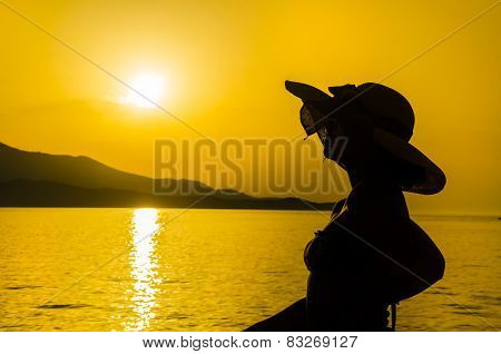Woman with hat silhouette on the beach at sunset