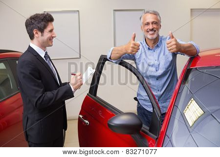 Smiling customer giving thumbs up at new car showroom