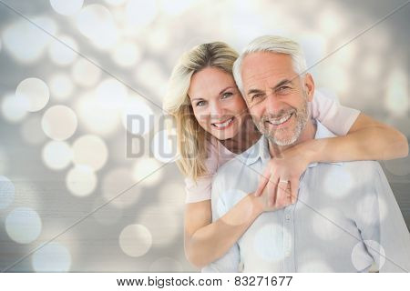 Smiling couple embracing and looking at camera against light circles on bright background