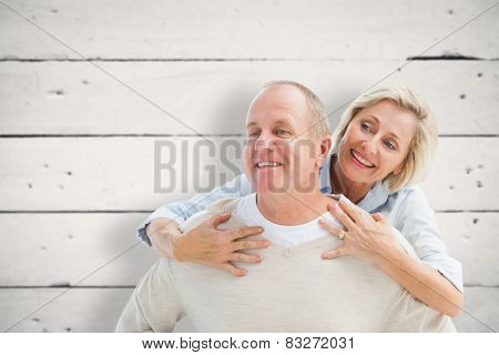 Happy mature man giving piggy back to partner against white wood