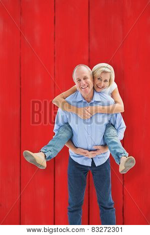 Mature man carrying his partner on his back against red wooden planks