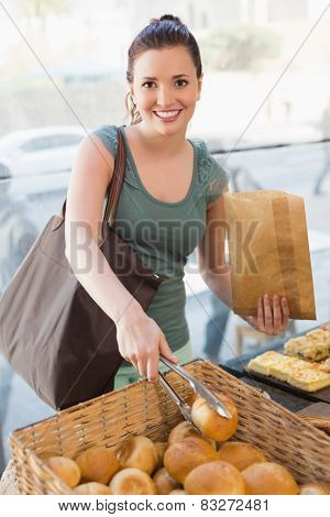 Pretty brunette picking out bread roll at the bakery