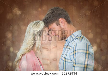 Attractive couple standing touching heads against black abstract light spot design