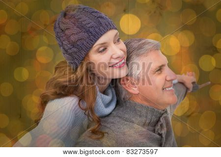 Carefree couple in warm clothing against close up of christmas lights