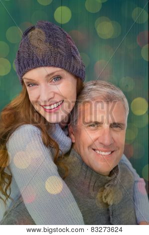 Happy couple in warm clothing against close up of christmas lights