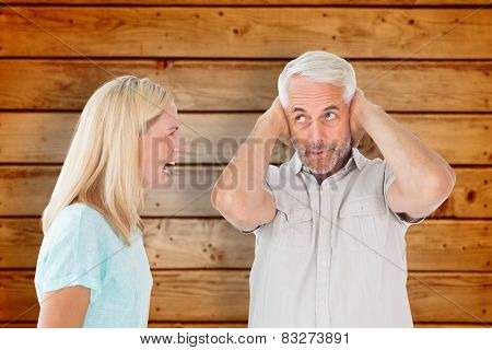Unhappy couple having an argument with man not listening against wooden planks background
