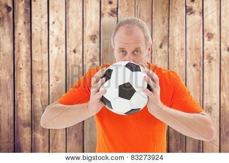Nervous football fan holding ball against wooden planks