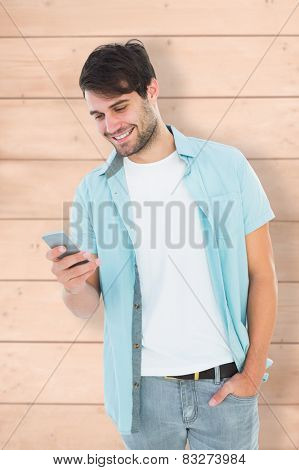 Happy casual man sending a text message against wooden planks