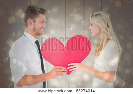 Attractive young couple holding red heart against black abstract light spot design