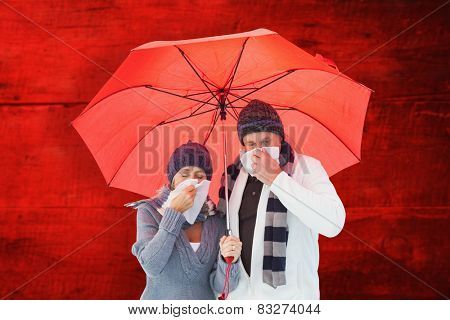 Mature couple blowing their noses under umbrella against red wooden planks