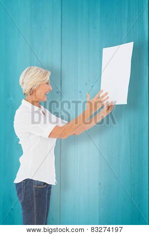 Angry woman shouting at piece of paper against wooden planks background