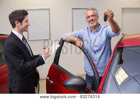 Smiling customer showing his new key at new car showroom