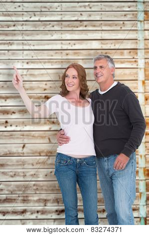 Casual couple walking and pointing against faded pine wooden planks